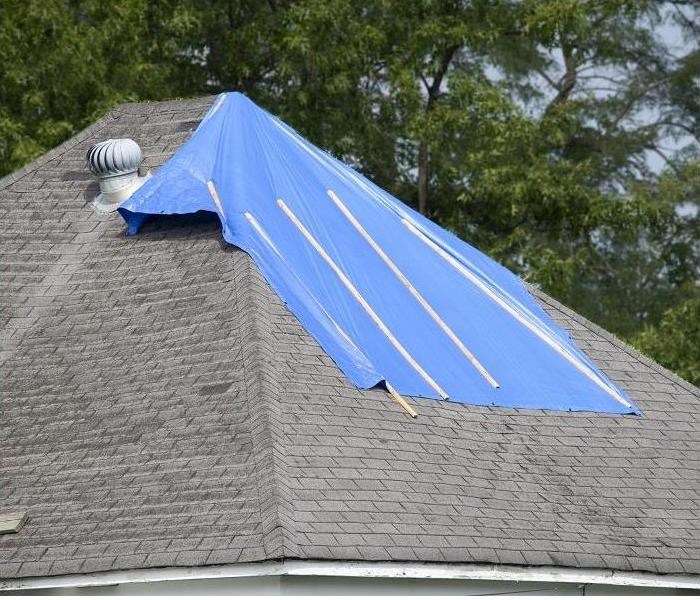 Tarp covering roof