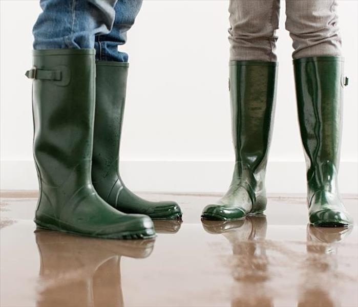 Two people standing with green boots on.
