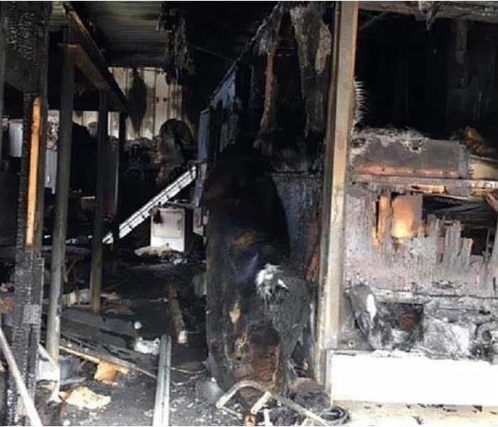 A garage in a home covered in soot and smoke damage after a fire disaster