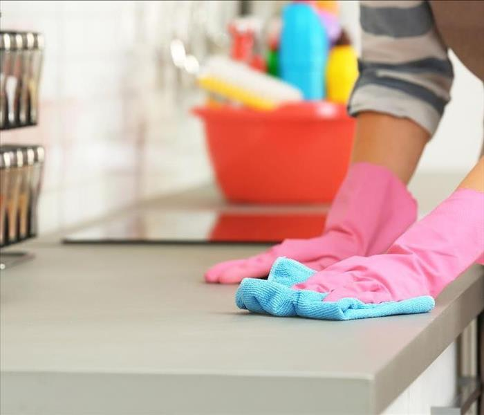 pink gloved hands wiping a grey counter top with a blue rag